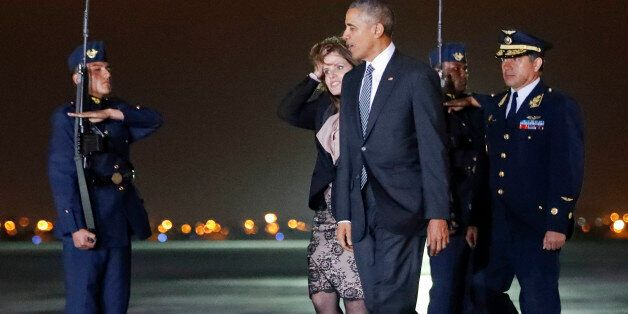 President Barack Obama walks across the tarmac with Second Vice President of Peru Mercedes Araoz, center,...
