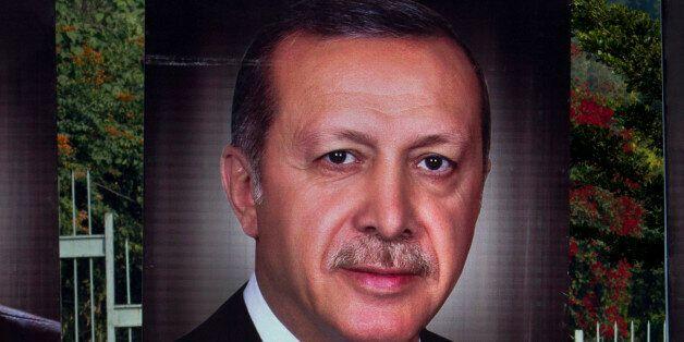 Pakistanis walk pasts billboards showing the portrait of Turkish President Recep Tayyip Erdogan, to welcome...