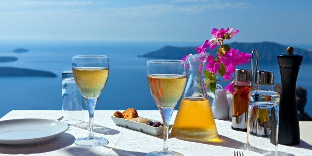 Table and glasses of wine for two people in the restaurant on the beach sea. Greece, Santorini island, view of the Caldera of the volcano.