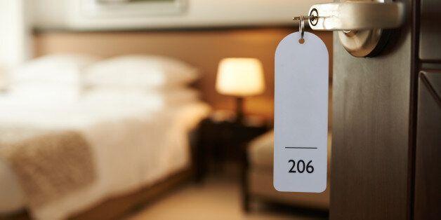 Opened door of hotel room with key in the