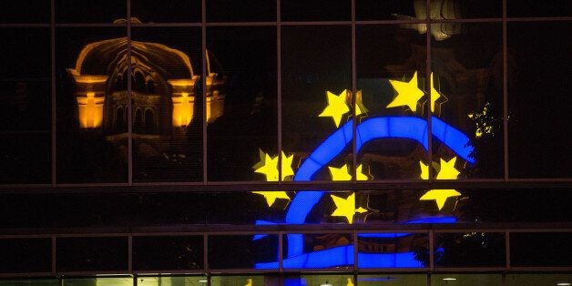 The euro sign sculpture is reflected in office windows as it stands outside the former European Central...