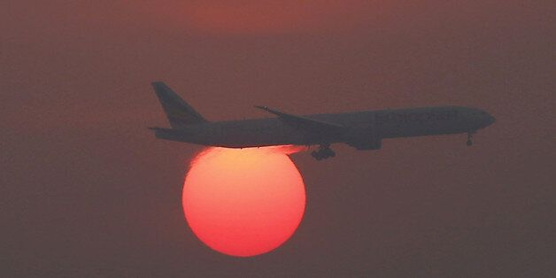 A plane flies over the setting sun in the sky at Beijing International Airport, China, March 2, 2016....