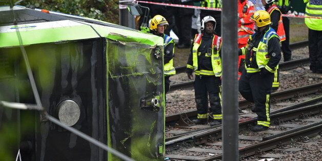 LONDON, ENGLAND - NOVEMBER 09: Members of London Fire Brigade look at the overturned tram at the site...