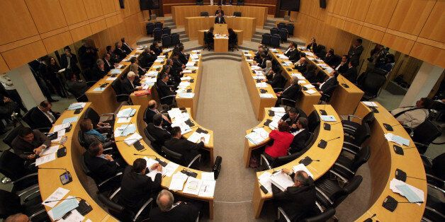 Cyprus members of parliament vote to approve a bill to restructure the island's troubled banking sector,...