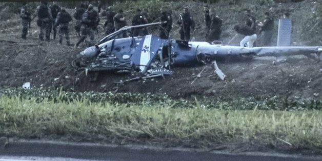 A screen shot taken from a video shows police officers investigating the crashed police helicopter that...