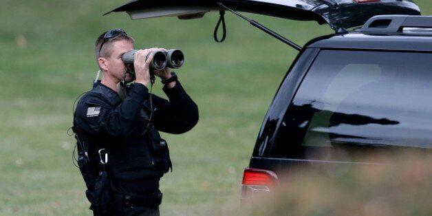 A police officer watches through binoculars near St. Charles Borromeo Seminary where Pope Francis will...