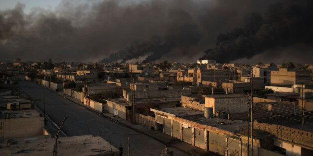 A man rides his bike on a street as smoke rises from burning oil fields in Qayara, some 50 kilometers...