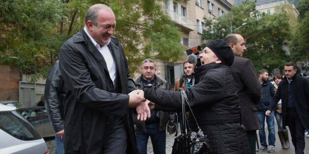 Georgian President Giorgi Margvelashvili, left, is greeted by a Georgian woman outside a polling station...