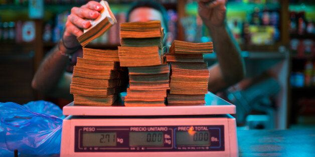 A manager weighs banknotes on a scale at a bakery in Caracas, Venezuela, on Thursday, Oct. 13, 2016....