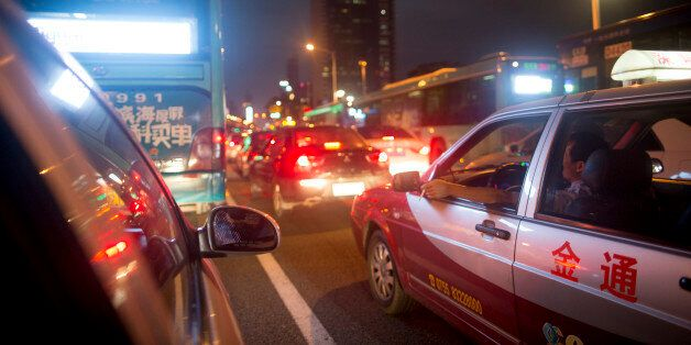 A taxi driver smokes a cigarette while waiting in traffic at night in the Luohu district of Shenzhen,...