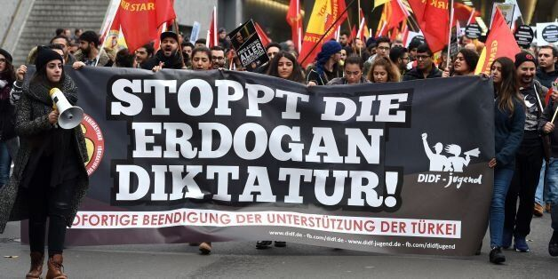 People attend a pro-Kurdish demonstration with a banner reading 'Stop Erdogan's dictatorship' in Cologne,...
