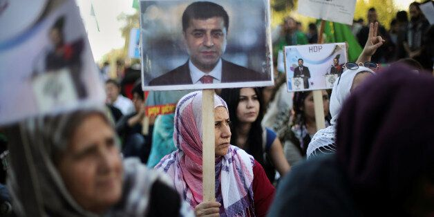 A Kurdish woman living in Greece holds a photo of arrested HDP co-leader Selahattin Demirtas, during...