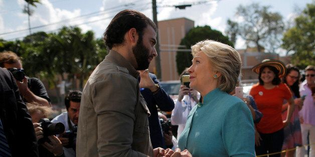 U.S. Democratic presidential nominee Hillary Clinton talks to actor and singer Jencarlos Canela while...