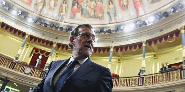 Spain's acting Prime Minister Mariano Rajoy looks back as he leaves his seat after the investiture debate...