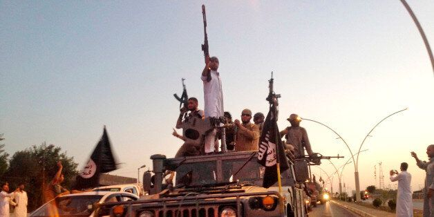 FILE - In this June 23, 2014 file photo, fighters from the Islamic State group parade in a commandeered...