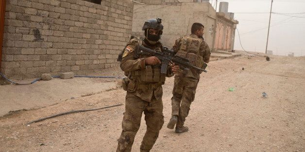 In this Tuesday, Nov. 1, 2016 photo, Iraqi special forces soldiers try to find cover as they take fire...