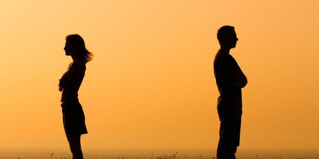 Silhouette of a angry woman and man on each other.