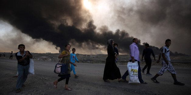 TOPSHOT - Displaced Iraqi families arrive near a checkpoint east of Mosul as they flea areas of unrest,...