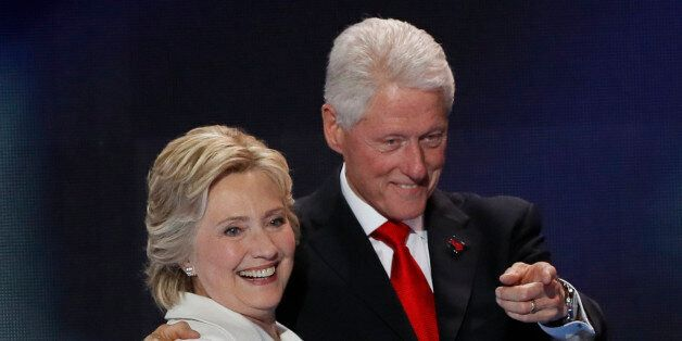 Democratic presidential nominee Hillary Clinton stands with her husband, former president Bill Clinton,...