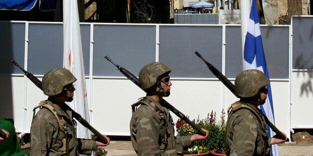 Cypriot soldiers stand with their guns in front of a temporary barrier after a wall was removed from...
