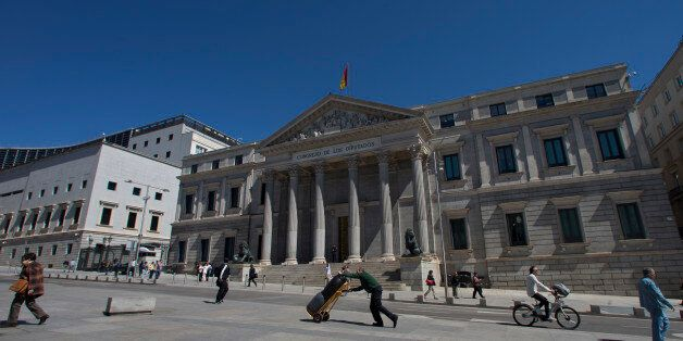 FILE - In this Tuesday, May 3, 2016 file photo, a worker pushes a trolley past the Spanish Parliament...