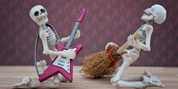 Skeleton poses with broom as playing guitar