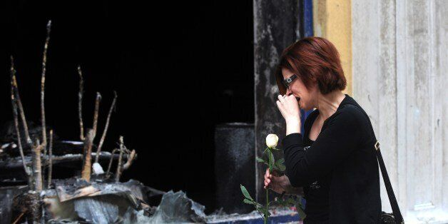 A woman cries as she puts flowers on May 6, 2010 in front a branch of the Marfin bank where three people...