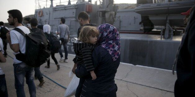 A Syrian refugee carries a baby as she and other refugees and migrants wait to board a passenger ship...