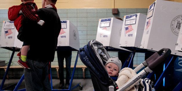 NEW YORK, NY - NOVEMBER 8: A baby waits as people vote at a polling site at Public School 261, November...