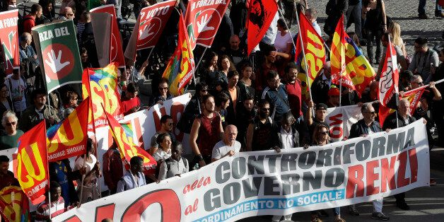 People march through downtown Rome to protest Matteo Renzi's government politics, Saturday, Oct. 22,...