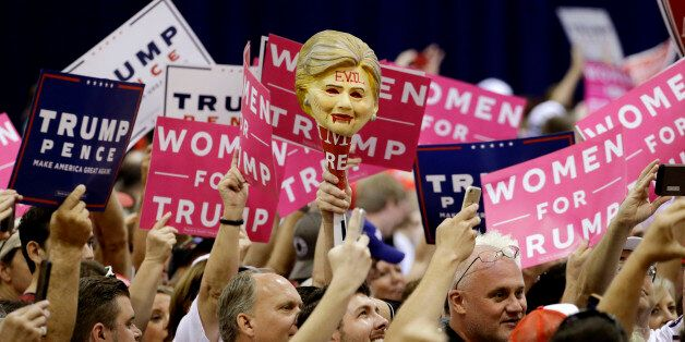 A supporter holds up a mask representing Democratic presidential candidate Hillary Clinton before a rally...