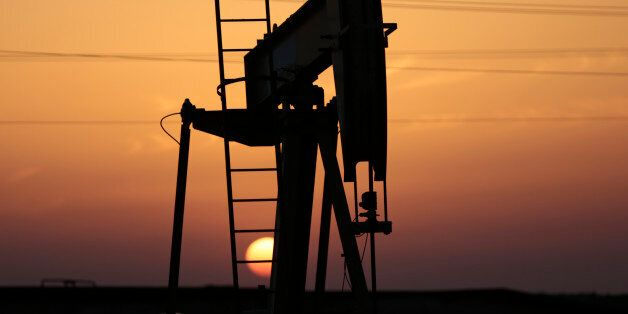 FILE -- In this April 16, 2016 file photo, an oil pump works at sunset in the desert oil fields of Sakhir,...