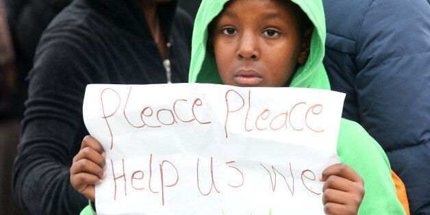 A young migrant poses with a poster reading 'Please please help us we are children' at the 'Jungle' migrant...