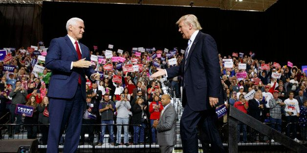 Republican presidential nominee Donald Trump, right, shakes hands with vice presidential candidate Gov....