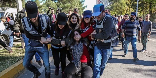 TOPSHOT - Turkish police officers detain Sabahat Tuncel (C), former Pro Kurdish People's Democracy Party...