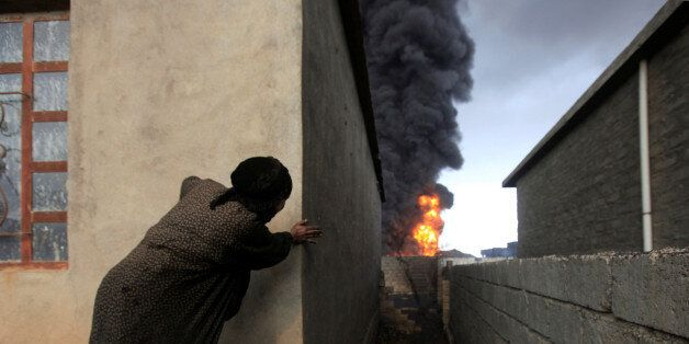 A woman looks at fire and smoke from oil wells set ablaze by Islamic State militants before the fled...