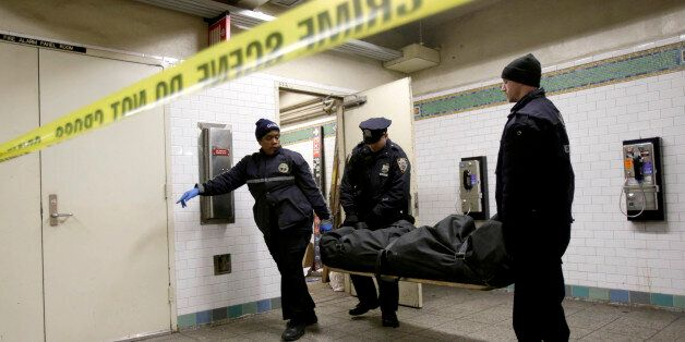 A police officer and medical examiner personnel carry a body out of a Times Square subway station in...