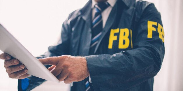 FBI agent, man working in the office on a crime. Using documents for