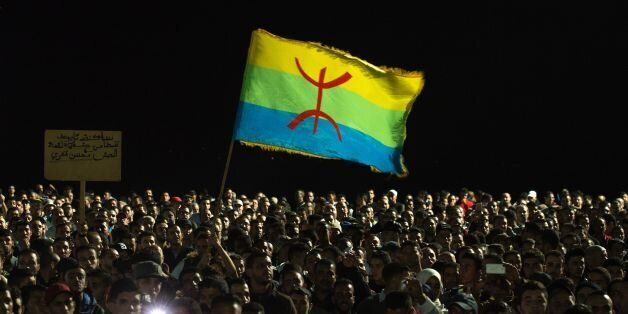 Protesters hold the Amazigh (Berber) flag as they shout slogans in the northern city of Al Hoceima on...