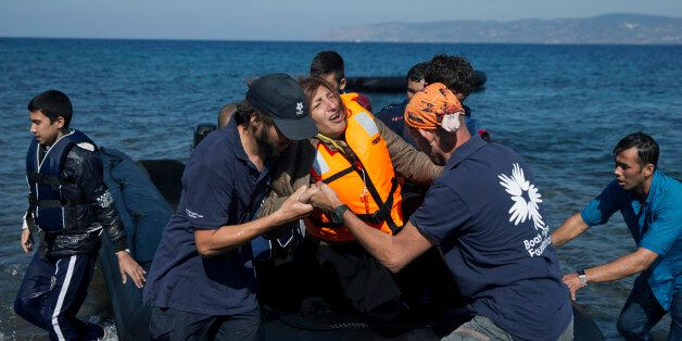 Volunteers help an Afghan woman after she arrive aboard a dinghy from Turkey, to the island of Lesbos,...