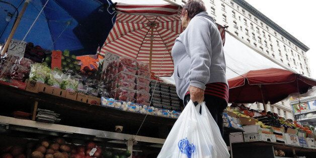 A woman carrying her supermarket purchase in plastic bags stops at a produce vendor on New York's Upper...