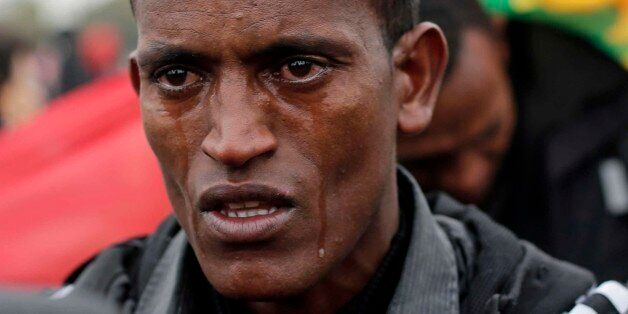 A 16-year-old migrant from Ethiopia cries as he waits to register at a processing centre in the makeshift...