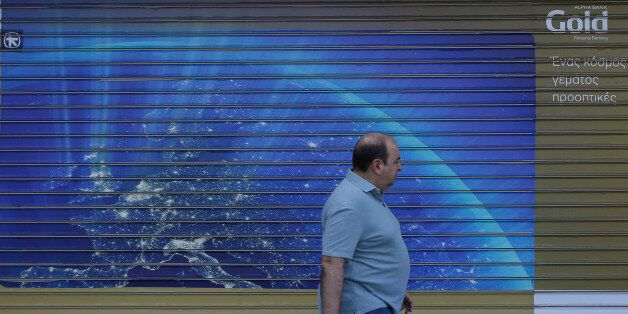 A man passes a closed bank with a shutter dipicting the European map, in Athens, Monday, June 29, 2015....