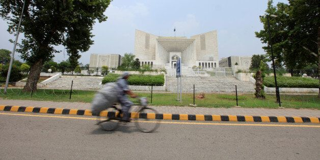 A man rides a bicycle past the Supreme Court building in Islamabad, Pakistan, June 27, 2016. Picture...