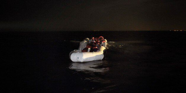 Refugees and migrants wait to be rescued from their sinking rubber boat some eight nautical miles off...