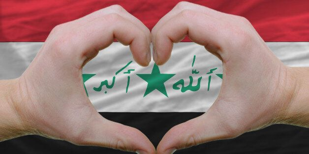 Gesture made by hands showing symbol of heart and love over iraq
