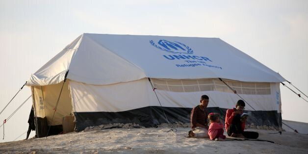 Youth sit outside a UNHCR tent at a refugee camp housing Iraqi families who fled fighting in the Mosul...