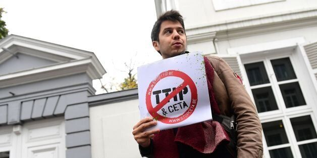 A demonstrator holds a poster reading 'Stop TTIP - Stop CETA' ahead of an emergency meeting of all Belgium...