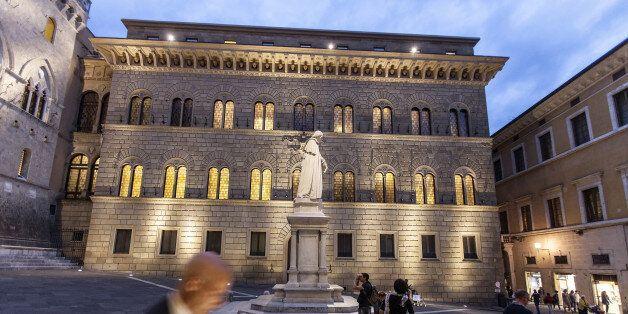 A pedestrian checks his smartphone device in Piazza Salimbeni, as the statue of Sallustio Bandini, an...