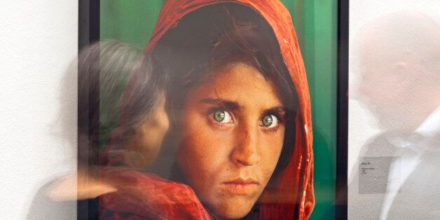 In this picture taken with a long time exposure people walk in front of the photo 'Afghan Girl' (Pakistan,...